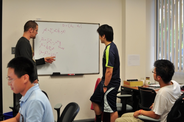 Kuan Liu(the right one in white T-shirt) was discussing one major problem with other PhD students in his office.